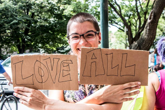 """Mazzoni Center - Person holding 'Love All' sign"" by the Philadelphia Bar Foundation's nonprofit partner, Mazzoni Center"