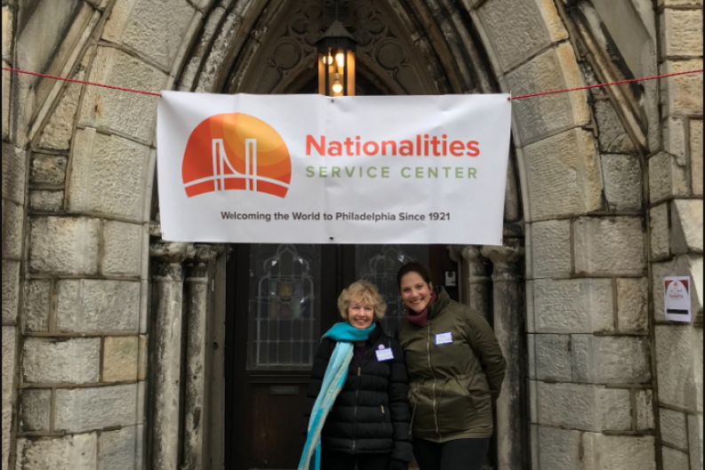 Two female employees smiling & standing in front of a Nationalities Service Center banner