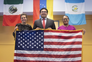 Three EILS staff members holding American flag.